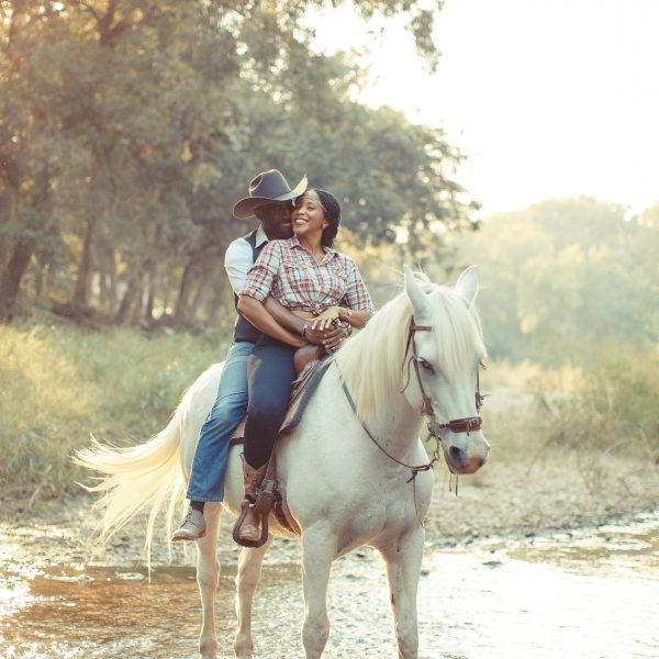 Large white gelding Maverick, our half Arabian and half Percheron draft cross is a great horse to use for photo shoots like this one, with couple posed riding doubles and posing for a kiss in the middle of Round Rock's Brushy Creek on a trail ride