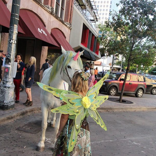 Blue and green mane sported here with gigantic unicorn and bareback riding woodlands fairy at 2016 sxsw festival in Austin TX