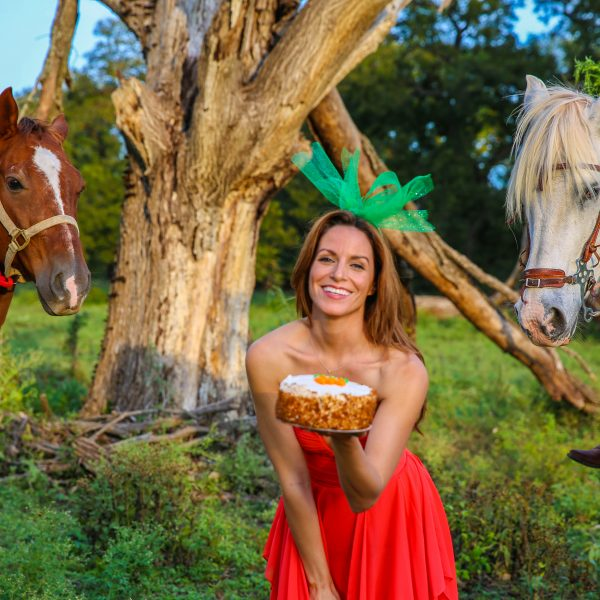 Beautiful horse model with orange dress and green head piece reminiscent of a carrot teases hungry horses in the background, in the middle of green fields at a Round Rock horseback riding lesson stables in Texas