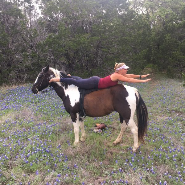 Horse trainer and yoga proactitioner dressed in red and blue on black and white paint mare in a field of Texas blue bonnets at Parrie Haynes in Killeen Texas