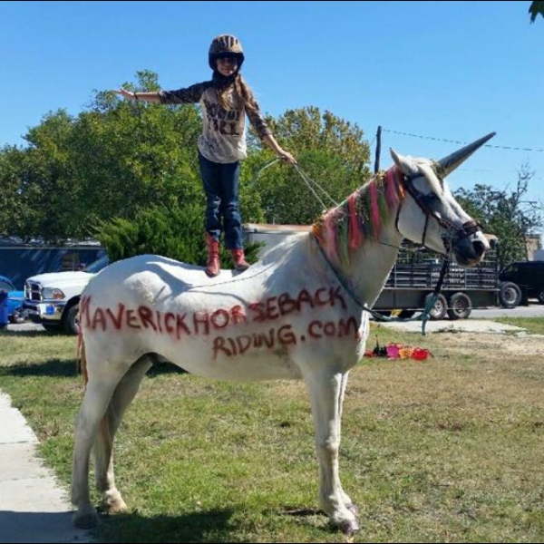 Here's the official sxsw unicorn posing with horse summer camper MaKenna, at the Hutto old tyme days festival community event