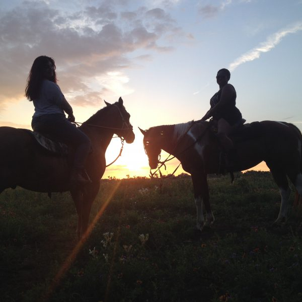 "Two riders pose in the sun set on tri color paint gelding, former barrel racer ""Izzy"" and AQHA gelding, chestnut love, Rocky, who helps us with equestrians of all skill levels"
